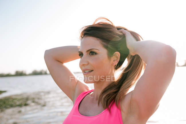 Portrait of attractive young woman with hands in hair looking sideways outdoors — Stock Photo