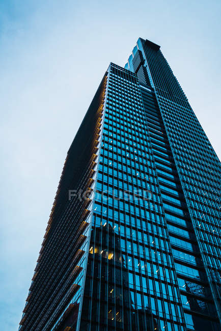 Tall skyscraper with glass walls at dusk — Stock Photo