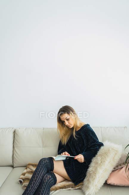 Junge Frau liest Buch zu Hause auf dem Sofa — Stockfoto