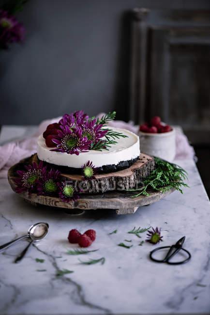 Delicioso pastel decorado con flores frescas en bandeja de madera - foto de stock