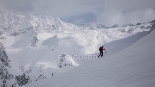 Vista lateral de excursionista irreconocible con palos caminando en la colina nevada. - foto de stock