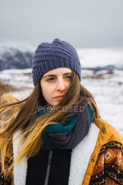 Woman in warm clothing standing in cold nature and looking away — Stock Photo