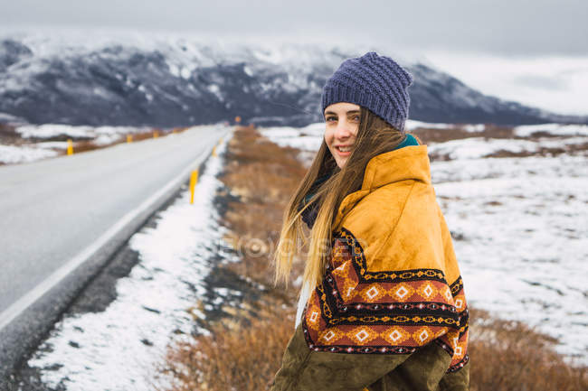 Woman in warm clothing standing in cold nature at roadside — Stock Photo
