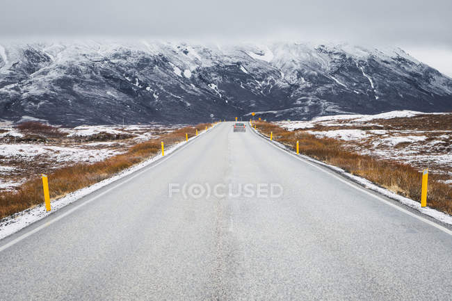 Road in countryside with snow covered mountains on background, Iceland — Stock Photo