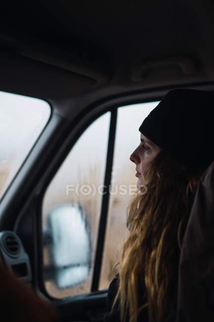 Mujer con sombrero sentada dentro del coche en el asiento de pasajeros - foto de stock