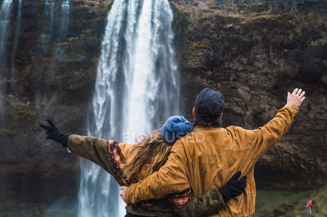 Couple standing in front of waterfall together — Stock Photo