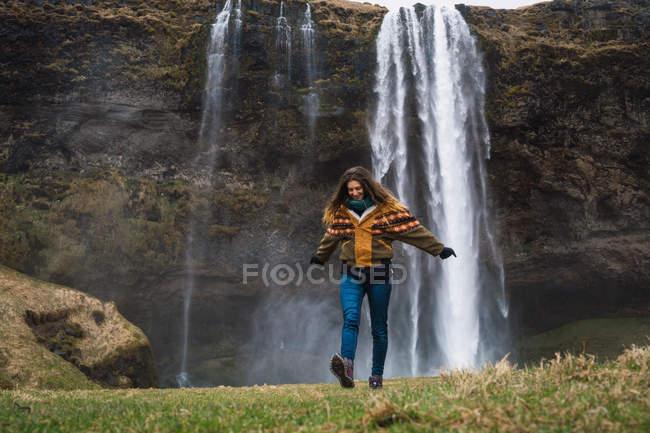Frau zu Fuß vor Wasserfall mit ausgestreckten Armen — Stockfoto