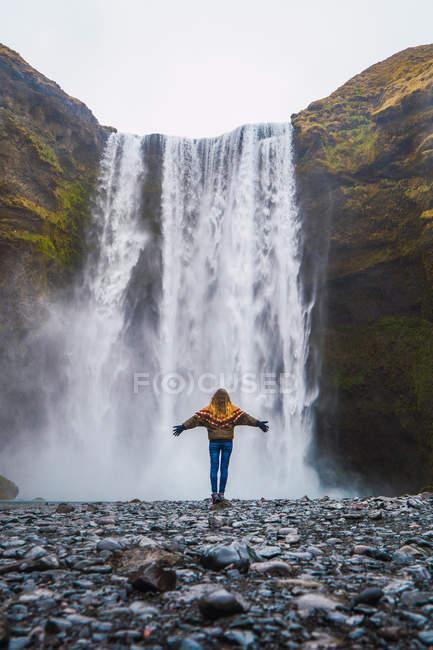 Frau stand vor Wasserfall mit ausgestreckten Armen — Stockfoto