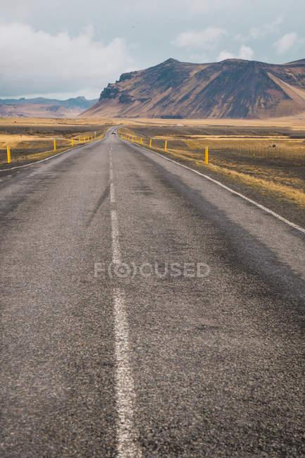 Estrada asfaltada na planície com altas montanhas, em fundo, Islândia — Fotografia de Stock
