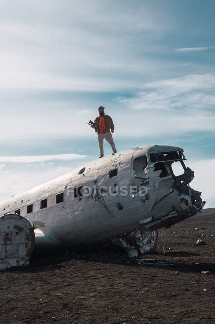 Male photographer standing on wrecked plain in nature, Iceland — Stock Photo