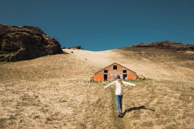 Femme debout sur une colline près d'une grange en bois — Photo de stock