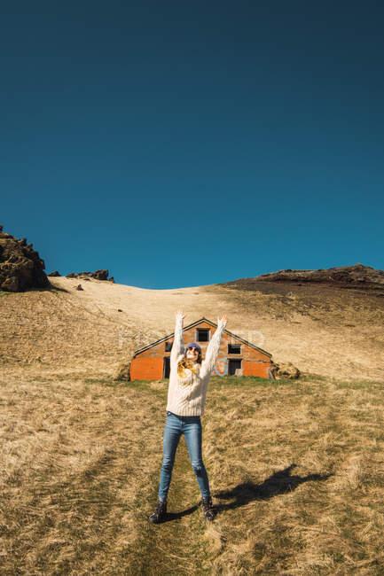 Femme aux bras levés debout sur une colline près d'une grange en bois — Photo de stock
