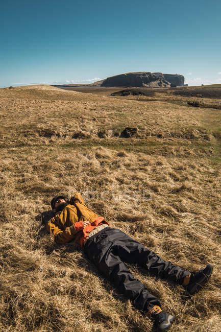 Homme barbu en vêtements chauds couché sur l'herbe sèche dans la campagne — Photo de stock
