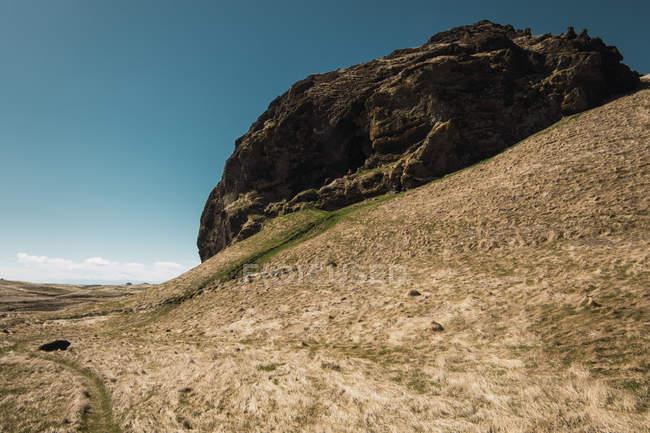 Énorme rocher dans les collines sous le ciel bleu, Islande — Photo de stock