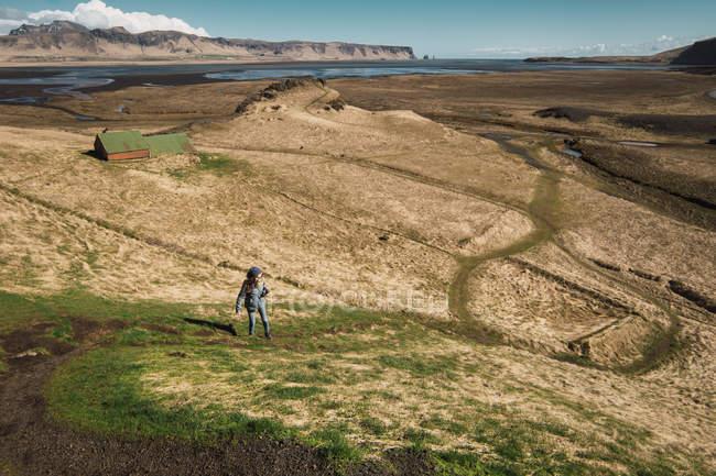 Femme debout dans la vallée avec des montagnes et un lac sur le fond, Islande — Photo de stock
