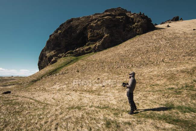 Homme veste à capuche avec caméra debout sur la vallée par temps ensoleillé, Islande — Photo de stock
