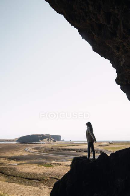 Silhouette de femme debout sur la montagne creuse dans l'ombre et levant les yeux — Photo de stock