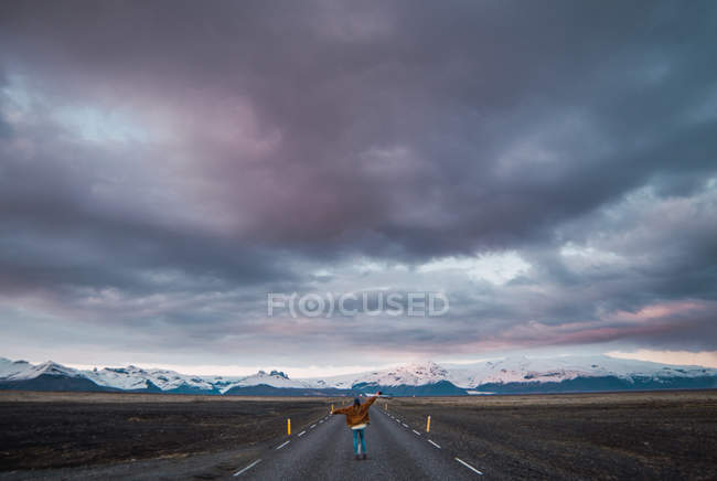 Женщина стоит на дороге в сельской местности с горами на заднем плане — стоковое фото
