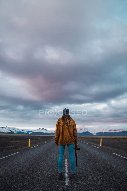 Woman standing on road in countryside with camera and looking at view — Stock Photo