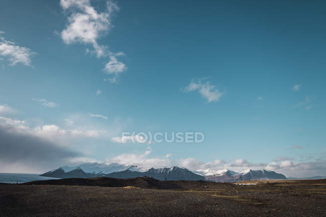 Landscape of field and snowy mountains under blue sky and white clouds, Iceland — Stock Photo