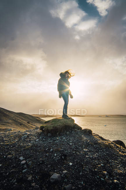 Woman standing on rock with view of sea and clouds in sunlight — Stock Photo