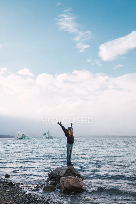 Woman balancing on rock in sea with outstretched arms — Stock Photo