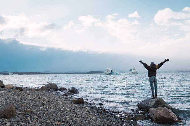 Girl standing on rock in sea and looking at view — Stock Photo
