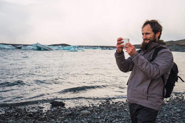Heureux voyageur barbu avec sac à dos prendre photo avec le smartphone en se tenant debout sur la plage de galets, Islande — Photo de stock