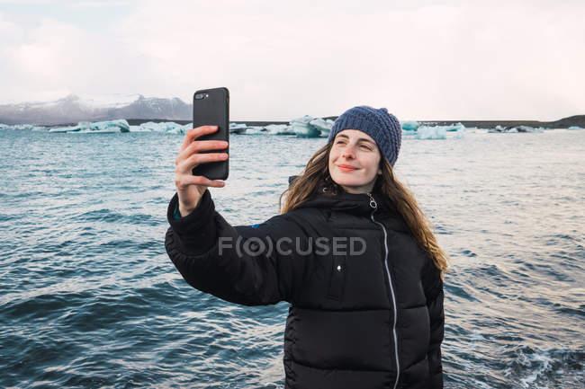 Lächelnde junge Frau unter Selfie auf kalten Strand — Stockfoto