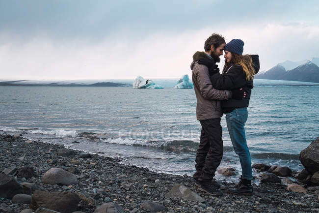 Loving couple standing on cold seascape face to face — Stock Photo