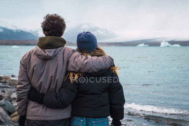 Loving couple standing on cold seascape and looking at view — Stock Photo