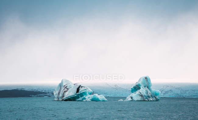 Vista à distância dos glaciares na água azul do oceano — Fotografia de Stock