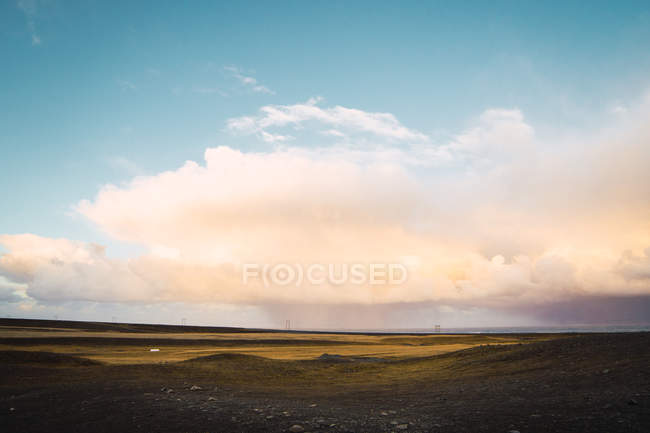 Silent remote green plain under glowing clouds in blue sky, Iceland — Stock Photo