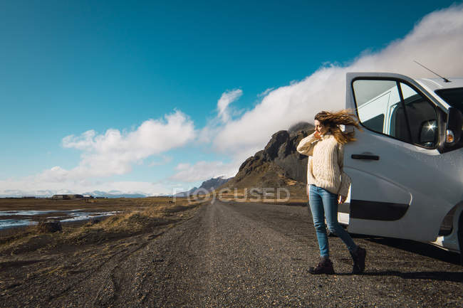 Woman standing near traveling bus in mountains, Iceland — Foto stock