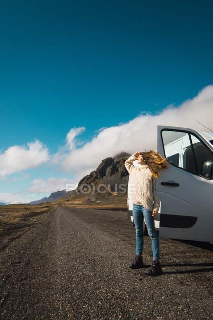 Femme debout près de voyage bus en montagnes, Islande — Photo de stock