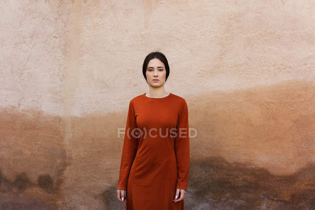 Woman standing against brown wall — Stock Photo