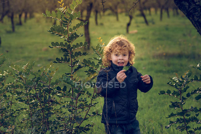 Boy with green leaf standing in park — Stock Photo