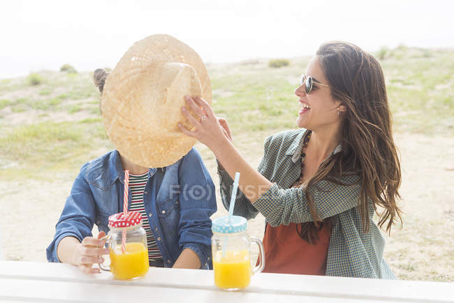 Women having fun with straw hat — Stock Photo