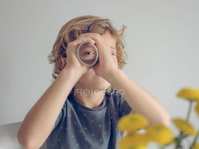 Charming boy en traje casual mirando a la cámara a través del tubo de papel mientras está sentado en el fondo blanco - foto de stock