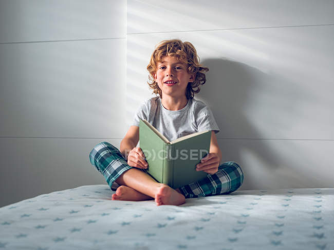 Boy in pajamas reading book — Stock Photo