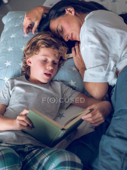 Mutter schläft und Sohn liest Buch — Stockfoto