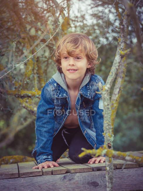 Pequeño niño agachado en valla - foto de stock