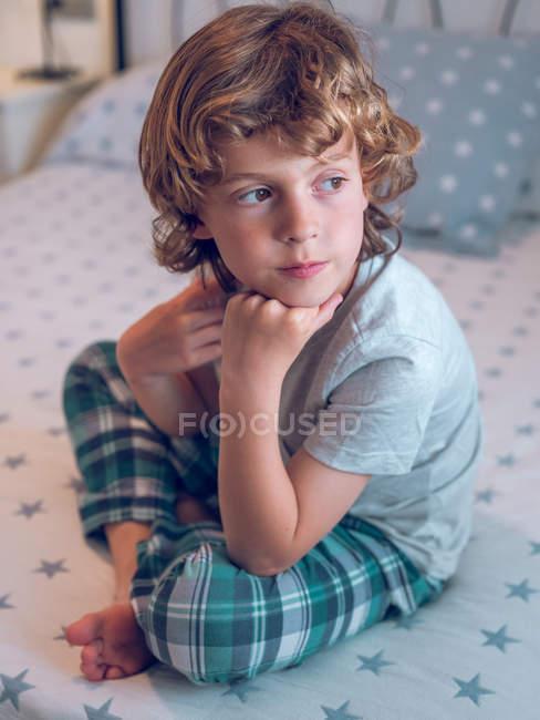 Menino sentado na cama — Fotografia de Stock