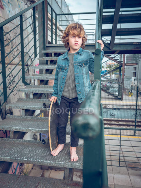 Barefoot boy standing on stairs — Stock Photo