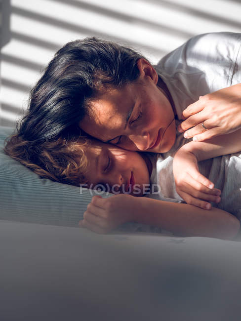 Mãe deitada na cama e abraçando filho — Fotografia de Stock