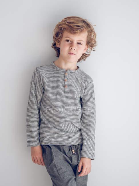 Élémentaire âge garçon penché sur mur et regarder dans caméra à l'intérieur . — Photo de stock