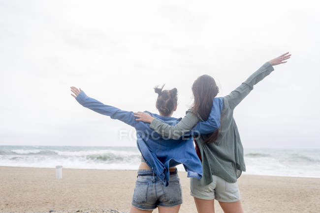 Female friends embracing on beach — Stock Photo
