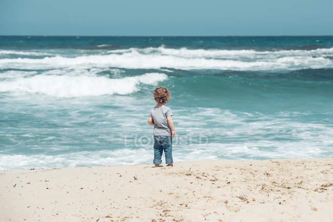 Хлопчик стоїть на пляжі — стокове фото