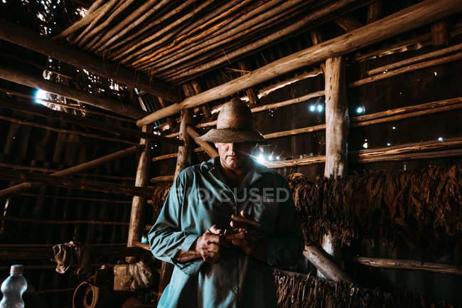 La Habana, Kuba - 1. Mai 2018: Lokale Mann Rauchen Zigarre unter Tabak Blätter trocknen im Bauernhof Scheune — Stockfoto