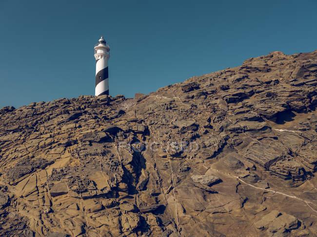 Tour de phare sur colline rocheuse — Photo de stock